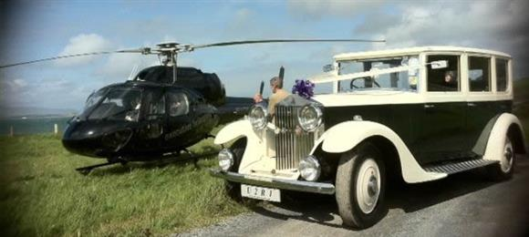 Vintage wedding Car Hire - A vintage Rolls Royce next to a small, black chopper